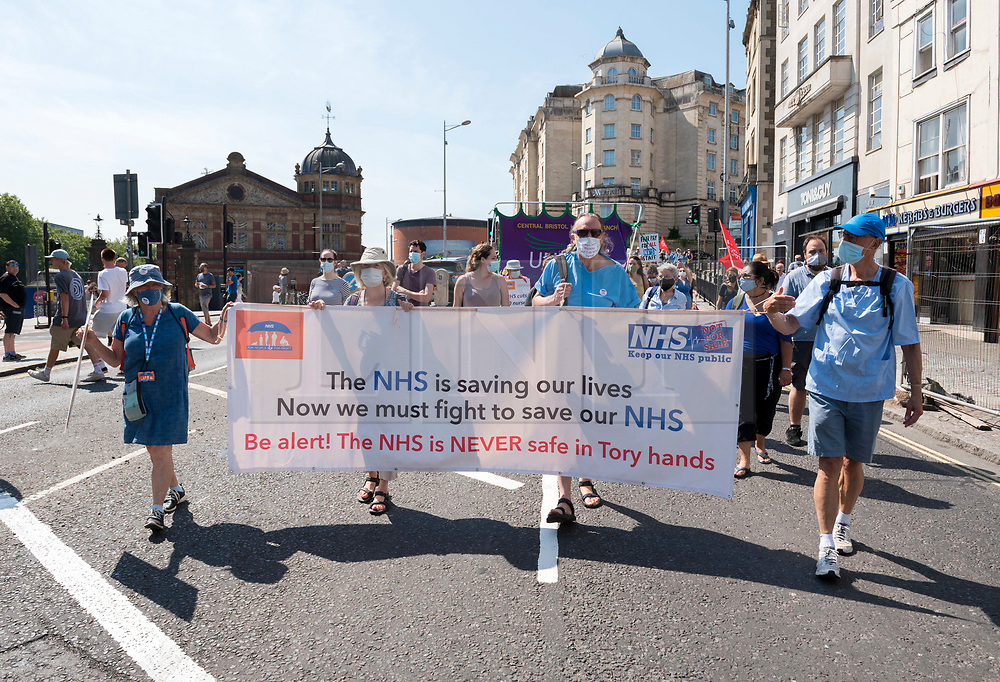 """© Licensed to London News Pictures; 08/08/2020; Bristol, UK. NHS Workers say NO! at a 'Bristol for Pay Justice' rally and march held in solidarity with health and social care workers across the UK demanding fair recognition of everyone in the NHS family and their tireless work throughout the pandemic. The campaign says """"If you clapped for us, please come and stand with us."""" The campaign says it is a disgrace that so many health and social care staff who worked so hard and risked their lives have been overlooked in the public sector pay rise, and that without nurses, health care assistants, porters, cleaners and the whole NHS family the UK could not have made it through. The campaign says that for too long this work has been underpaid and undervalued and now the UK government is squeezing the NHS from all sides; they say NO to privatisation, deliberate underfunding, low wages and poor conditions. Organisers asked that all attendees respect social distancing as much as possible and with a planned route that gives as much space as possible and that mask wearing will be mandatory with masks available on the day for those that don't have them. Attendees are asked to wear blue, or a blue ribbon in solidarity. Photo credit: Simon Chapman/LNP."""