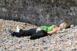 © Licensed to London News Pictures. 30/04/2015. Brighton, UK. A woman sunbathing on Brighton Beach, today Thursday April 30th 2015. Photo credit : Hugo Michiels/LNP