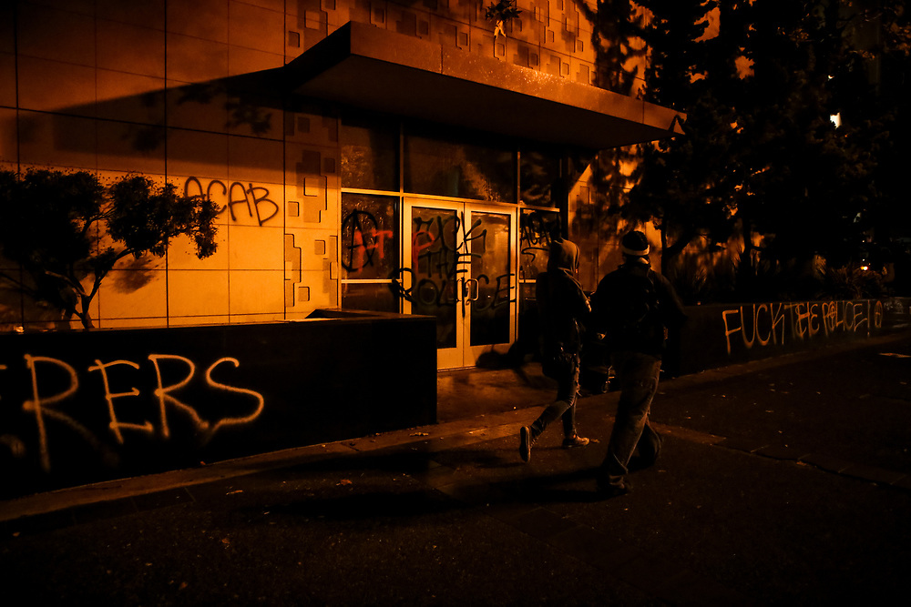 Two individuals walk past the Oakland Police Department headquarters after it was damaged and vandalized during a protest following the deaths of Alton Sterling and Philando Castile, who were fatally shot by police officers, in downtown Oakland, Calif., Thursday, July 7, 2016.<br /> <br /> Sterling was shot by two white Baton Rouge Police Department officers in Baton Rouge, Louisiana and Castile was shot by a St. Anthony police officer in Falcon Heights, Minnesota.