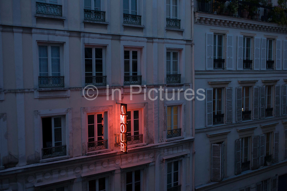 """Neon sign outside the Amour Hotel at 8 rue Navarin, 9th Arrondissement, Paris, France. Seen from another hotel on the same street, we see the glow of the letters showing the name of this trendy address in central Paris, the French capital. The Amour is one of the first designer budget hotels is still going strong in the South Pigalle (aka """"SoPi"""") district, with its unique artist-decorated rooms that focus more on style than useless amenities."""