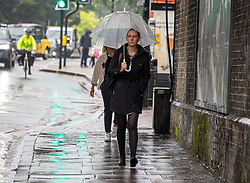 Licensed to London News Pictures. 14/09/2021. London, UK. Commuters brave the rain this morning on their way to work in Putney south-west London as weather forecasters issue yellow weather warnings for heavy rain and thunderstorms for London and the South East today with the potential of flooding to homes and businesses and disruption to travel networks. However, sunny warm weather is expected from tomorrow with highs of 24c. Photo credit: Alex Lentati/LNP