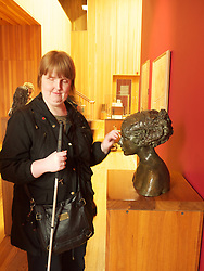 Visually impaired woman at sculpture exhibition at Walsall Art Gallery