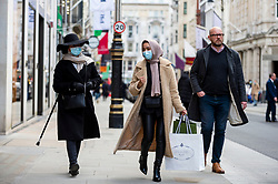 © Licensed to London News Pictures. 12/04/2021. LONDON, UK.  People carrying their shopping in Mayfair following the UK government's coronavirus roadmap out of lockdown which allowed non-essential shops to reopen today.  Photo credit: Stephen Chung/LNP