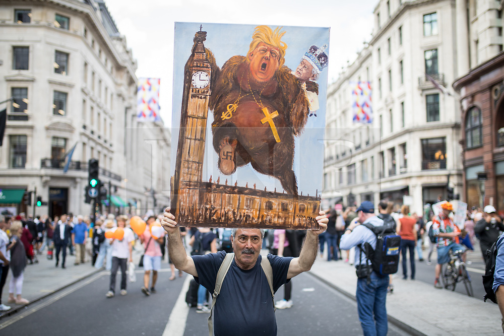 © Licensed to London News Pictures. 13/07/2018. London, UK. Satirical artist Kaya Mar poses with his painting of Donalrd Trump, as tens of thousands of demonstrators march through central London to protest against the President of the United States, Donald Trump, and his ongoing four-day visit to the UK. The demonstration began at Portland Place and ended with a rally at Trafalgar Sqaure. Photo credit : Tom Nicholson/LNP