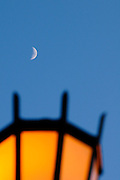 A quarter moon is seen above a lit lamp in Waikiki.