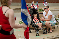 Xavier and Corianne Littizzio watch as the Laconia High School marching band goes down Main Street to Veteran's Square during Memorial Day services on Monday morning.  (Karen Bobotas/for the Laconia Daily Sun)
