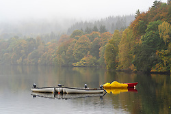 Autumn colours on trees and rowing boats on Loch Faskally in Pitlochry, Scotland, UK