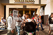 """22 OCTOBER 2011 - PHOENIX, AZ:    Occupy Phoenix protesters march past the Wells Fargo bank in Phoenix Saturday. The demonstrations at Occupy Phoenix, AZ, entered their second week Saturday. About 50 people are staying in Cesar Chavez Plaza, in the heart of downtown. The crowd grows in the evening and on weekends. Protesters have coordinated their actions with police and have gotten permission from the city to set up shade shelters and sleep in the park, but without tents or sleeping bags, which is considered """"urban camping,"""" instead protesters are sleeping on the sidewalk.     PHOTO BY JACK KURTZ"""