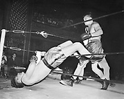 """Y-480803C-01. Pacific Coast Heavyweight Title fight at Auditorium. Roy Hawkins vs. Bill Petersen (winner). """"Good one of Petersen through ropes, ran AP"""". August 3, 1948. referee: Ralph Gruman. """"The crowd stood and screamed at the stoppage by the referee, and threw paper into the ring. Hawkins attempted to get at Gruman until his arms were pinioned by his handlers. He then tried to attack Peterson. Firemen and police restored order. Hawkins was knocked down in the 1st, and Petersen in the 5th round.""""(caption from Tacoma News Tribune)"""