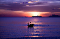 Boat silhouetted on the waters off China Beach near Hoi An in the colourful glow of a stunning sunrise.