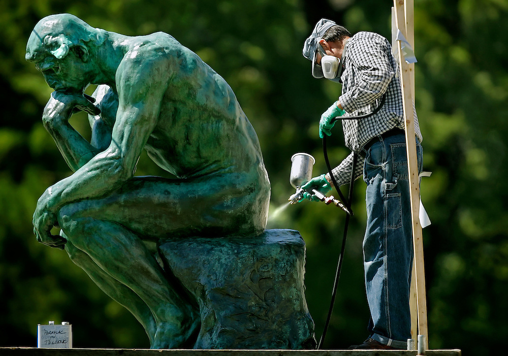 """Bob Marti, an art conservator with Russell-Marti Conservation Services of California, Mo., applied a coat of acrylic laquer by sprayer to a bronze sculpture of """"The Thinker,"""" by Auguste Rodin, in the Kansas City Sculpture Park on the south steps of the Nelson-Atkins Museum of Art in Kansas City, Mo. on September 13, 2006."""