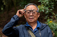 Chinese photographer demonstrating his photographing glasses, Wuliangshan Nature Reserve, Mount Wuliang Nature Reserve in Jingdong county, Yunnan, China