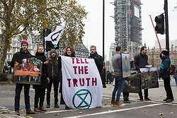 London, UK. 25th November, 2018. Environmental campaigners from Extinction Rebellion attend a Rebellion Day 2 event to highlight 'criminal inaction in the face of climate change catastrophe and ecological collapse' by the UK Government as part of a programme of civil disobedience during which scores of campaigners have been arrested. The event comprised a funeral ceremony in Parliament Square followed by a procession to Downing Street and Buckingham Palace.