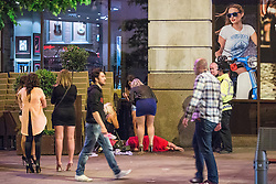 © Licensed to London News Pictures . 15/06/2014 . Manchester , UK . A woman lies on the pavement and is tended to by security and police . People on a night out in Manchester City Centre overnight , following England's defeat to Italy in the World Cup . Photo credit : Joel Goodman/LNP