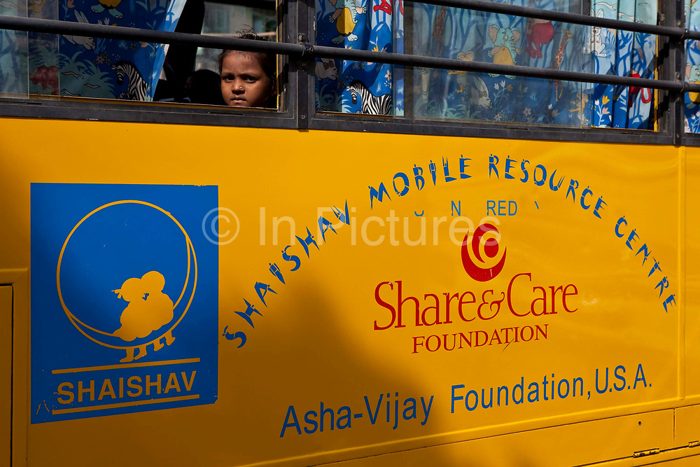 A child looks out of the window of one of the Mobile Resource Centre's run by the Shaishav Trust.  The Trust has 2 buses that are equipped with libraries, television; audiovisual equipment and learning resource materials. The buses visit 36 schools a week in the Bhavnagar region giving additional support and resources for education.