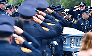 Officers salute the casket of slain San Antonio police offiocer MIGUEL MORENO during funeral services Friday in San Antonio. Moreno's assailant committed suicide shortly after the killing.