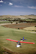 Ultra-light plane flying over the grape vineyards and hayfields of the Barossa Valley. South Australia.