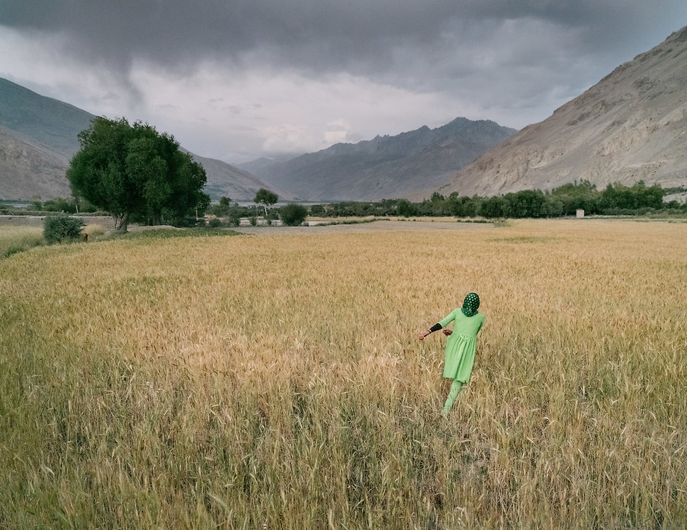 Girl wearing green in the wheat field. Family of Khon Jon, after a visit to their ancestor's grave. The traditional life of the Wakhi people, in the Wakhan corridor, amongst the Pamir mountains.