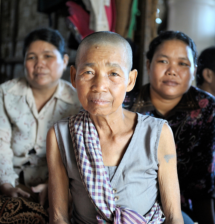 Members of a women's self-help group in the Phnom Penh neighborhood of Sen Rikreay, including Shum Lorn, 65 (center), listen raptly as a Buddhist monk addresses the group. Many people in this community are infected or affected by HIV and AIDS, and Buddhist monks and other religious meet with them regularly to mediate and discuss their challenges.
