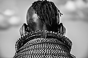 A portrait in black and white of a Turkana women wearing traditional stacked beaded necklaces with traditional hair covered in ochre and goat fat, Lake Turkana, Loiyangalani,Kenya, Africa