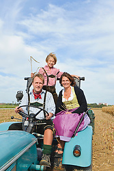 Family on tractor in cornfield, Bavaria, Germany