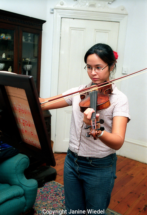 teenaged girl practicing the violin at home.