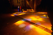 Stained glass light shines on to visitors and the floor of Palma's La Seu Cathedral in Mallorca.