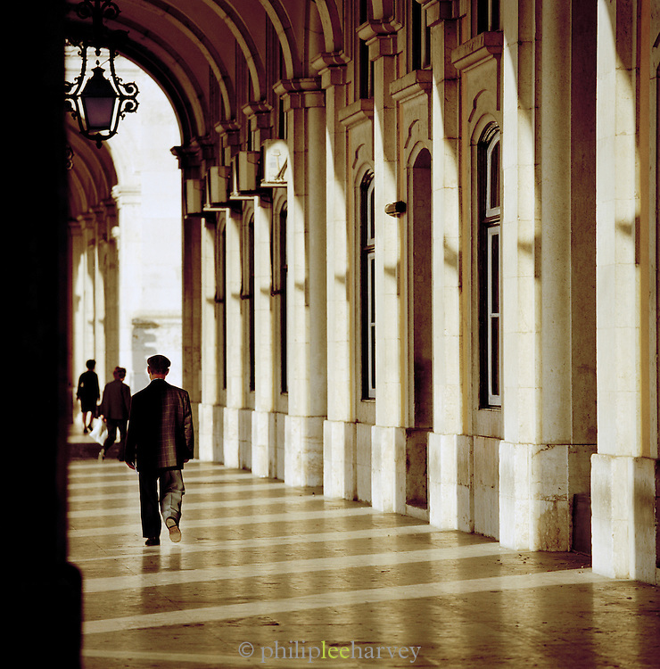 People walk through the arches at Praca do Comercio, Commerce Square, in Lisbon, Portugal