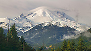 Clouds enveloped Mt Rainier for two days as it snowed at higher elevations and rained through the valleys.  The clouds lifted for a while on the third morning and the sun lit the fresh snow and fall colors in the valley. A lenticular cloud hung tight over the summit.