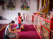 07 OCTOBER 2014 - GEORGE TOWN, PENANG, MALAYSIA: Women pray in the Goddess of Mercy shrine in the center of George Town (also Georgetown), the capital of the state of Penang in Malaysia. Named after Britain's King George III, George Town is located on the north-east corner of Penang Island. The inner city has a population of 720,202 and the metropolitan area known as George Town Conurbation which consists of Penang Island, Seberang Prai, Kulim and Sungai Petani has a combined population of 2,292,394, making it the second largest metropolitan area in Malaysia. The inner city of George Town is a UNESCO World Heritage Site and one of the most popular international tourist destinations in Malaysia.         PHOTO BY JACK KURTZ