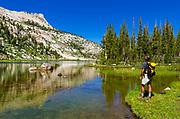 Hiker at Elizabeth Lake under Unicorn Peak, Tuolumne Meadows, Yosemite National Park, California USA