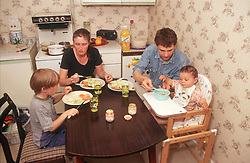 Family group sitting at kitchen table eating meal,