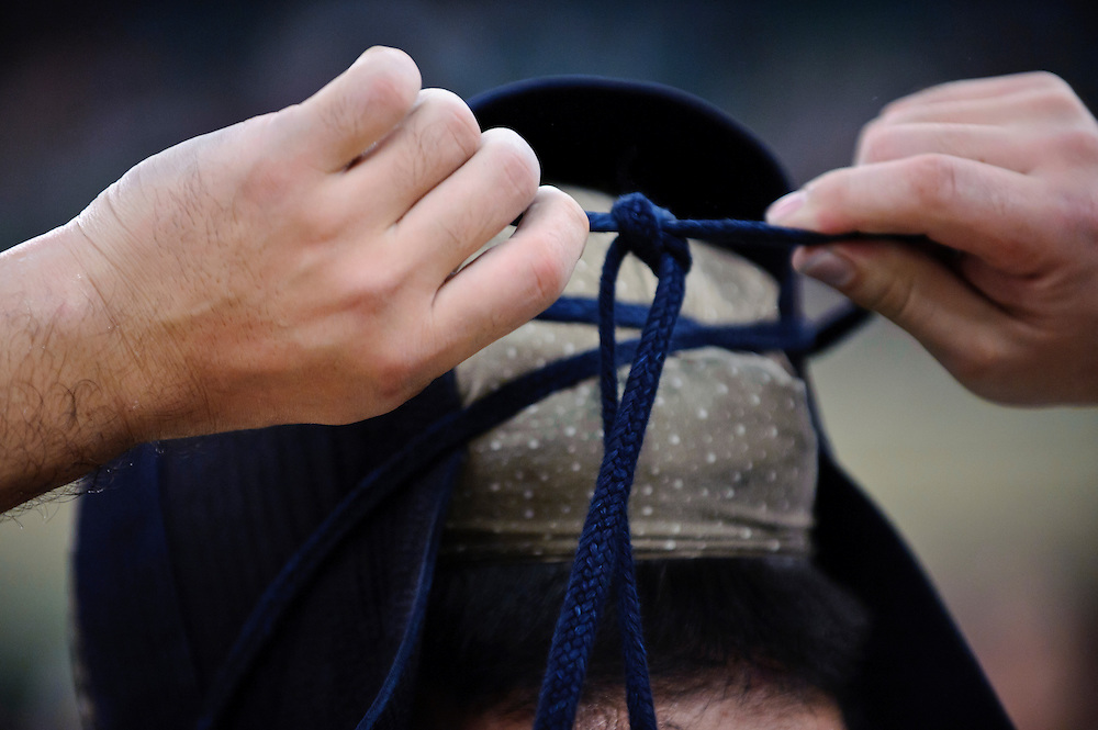 A contestant tying the laces of a kendo helmet, 59th All Kendo Championship,  Budokan, Tokyo, Japan, November 3, 2011. Contestants from all over Japan compete doing the day-long event. Kendo is a popular martial art based on traditional Japanese swordsmanship.