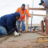 """112213  Adron Gardner/Independent<br /> <br /> Volunteers Elvivera Chicag, left, Gerald Chicag, center, and Rose Begay work away on a tile walkway and cedar fence for the United Navajo Way in Window Rock during the very first Day of Caring for the organization. More than 30 volunteers from Navajo Nation and Four Corners area were on hand for improvements to the United Navajo Way office.  """"We didn't mind the rain.  We didn't mind snow.  We just worked and had fun,"""" George Kelly of BHP Billiton mining in Farmington said."""