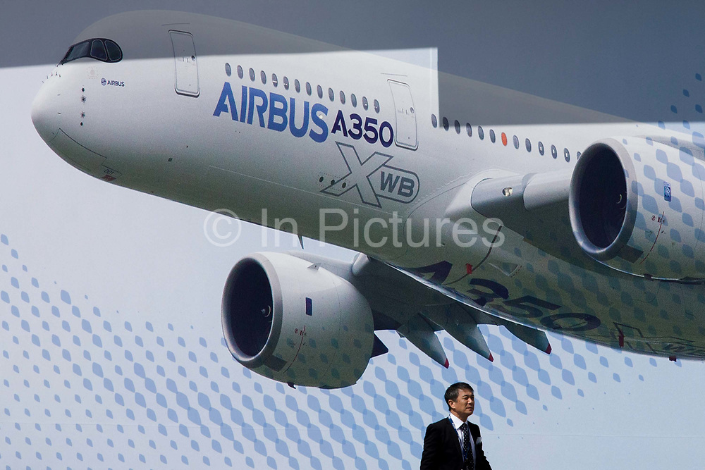 An Asian visitor passes beneath a large billboard of the Airbus A350 XWB on the side of the Airbus corporate chalet at the Farnborough Air Show, England. The A350 XWB is the only all-new aircraft in the 300-400 seat category. The A350 XWB is a family of long-range, two-engined wide-body jet airliners developed by European aircraft manufacturer Airbus. The A350 is the first Airbus with both fuselage and wing structures made primarily of carbon-fiber-reinforced polymer. It's scheduled to enter commercial service later in 2014.