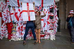 © Licensed to London News Pictures. 10/07/2021. LONDON, UK.  Women buy England flags in Piccadilly Circus ahead of the final of Euro 2020 between Italy and England tomorrow night Wembley Stadium.  It is the first major final that England will have played in since winning the World Cup in 1966 but Italy remain unbeaten in their last 33 matches.  Photo credit: Stephen Chung/LNP