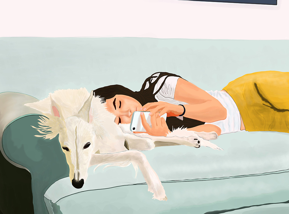 a young woman reclines on a couch with her iPhone and dog