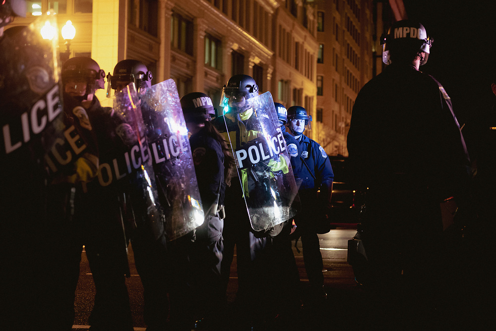 Washington DC, USA - January 19, 2017: Washington Metropolitan Police stand at the intersection of F and 13th Street NW holding shields during protest on the eve of President-elect Trump's inauguration.