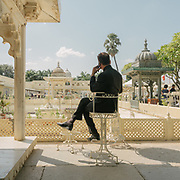 """A guest enjoys the view of the Jag Mandir, a palace built on an island in the Lake Pichola. It is also called the """"Lake Garden Palace"""". The palace is located in Udaipur city in the Indian state of Rajasthan. Its construction is credited to three Maharanas of the Sisodia Rajputs of Mewar kingdom."""