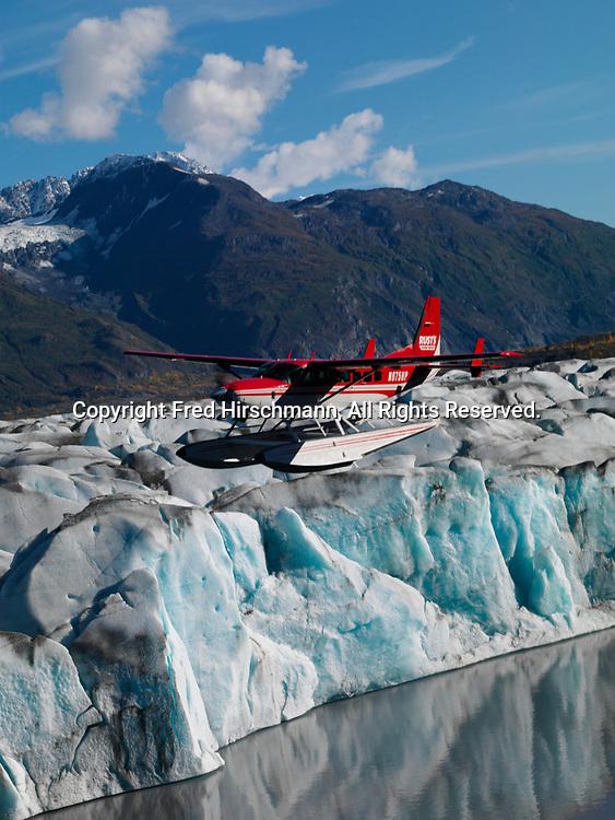 Rust's Flying Service Cessna 208 Caravan on floats flying above Knik Glacier, Lower Lake George, Alaska.