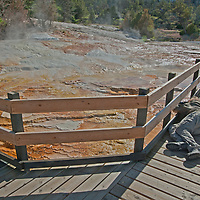 A photographer takes pictures of mineral deposits at Mammoth Hot Springs, Yellowtone National Park, Wyoming