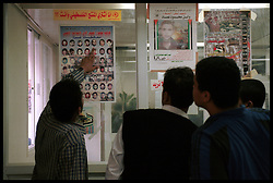 Palestinian men at Shifa Hospital in Gaza City, look for familiar faces on the wall of martyrs, those who have been killed during the Intifada. (Photo © Jock Fistick)