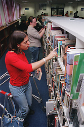 Teenage girl with physical disability looking through books in college library,