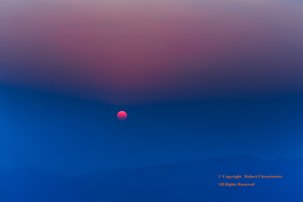 Red Over Blue: Mornings red sun rising over the blue, fog covered foothill ridges, Darjeeling India.