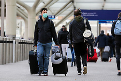 © Licensed to London News Pictures. 01/02/2020. London, UK. A man with suitcases arrive at Paddington Station from Heathrow Airport wearing a surgical face mask following the outbreak of Coronavirus in Wuhan, China. According to Twitter two people were taken to hospital from Paddington Station on the evening of Friday 31 January, amid fears that Coronavirus has speed to London. Part of the station was cordoned off following a woman sitting on a bench, while staff in face masks keep guard. Photo credit: Dinendra Haria/LNP