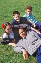 Multiracial group of youths lying on grass smiling,