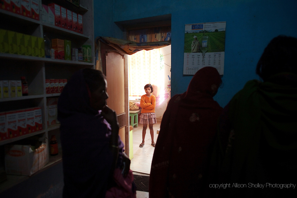 The daughter of clinic doctor Mira Kumari watches through an open doorway into the examination room as the family of Sugia Devi gathers around the table on which she lies, laboring with her first child at the clinic in the village of Mounia in the state of Bihar, India.  Sugia's labor lasted two full nights and involved three midwives and the village doctor. She eventually delivered a baby girl via Caesarian section in another local clinic-- the second she was brought to, as this one did not have the necessary resources.