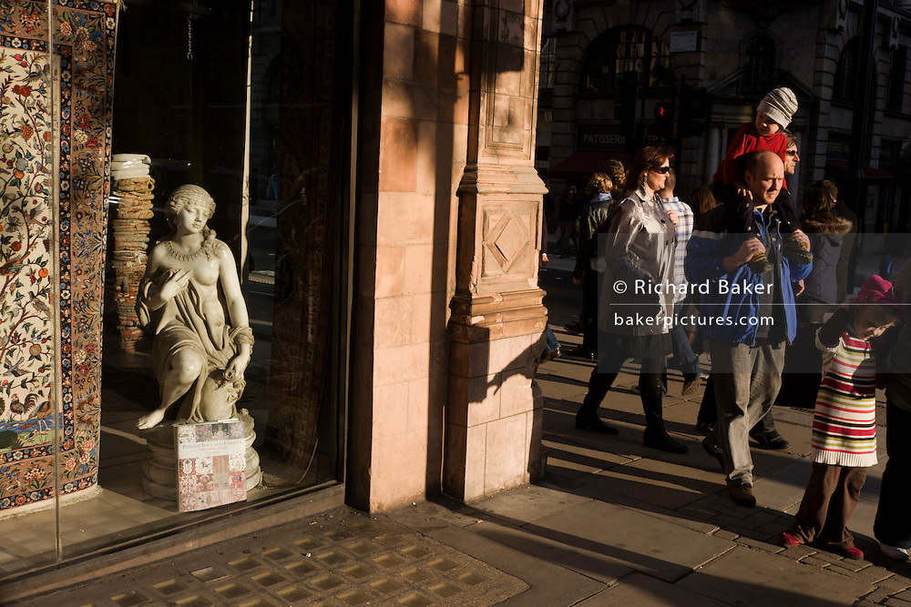 Young girl on dad's shoulders admires small girl statue credited to the 19th century Florence-born artist Raffaello Romanelli