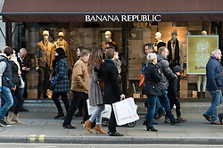 © Licensed to London News Pictures. 20/12/2014. London, UK. Christmas shoppers on London's Regent Street on the last saturday before Christmas walk past a storefront for Banana Republic. Photo credit : Richard Isaac/LNP