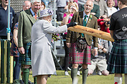 ABOYNE HIGHLAND GAMES CELEBRATES ITS 150TH ANNIVERSARY THIS YEAR AND THE QUEEN VISITED TO CELEBRATE THE ACHIEVEMENT<br /> PIC OF HER MAJESTY POURING WHISKY OVER A NEW GAMES CABER AT THE GAMES IN ABERDEENSHIRE<br /> PIC DEREK IRONSIDE / NEWSLINE MEDIA